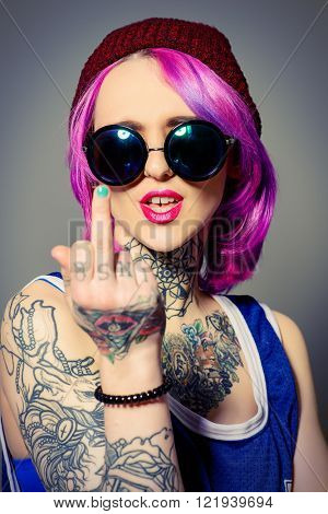 Style of modern youth. Expressive bright girl shows bad sign. Tattoo style. Hair coloring.