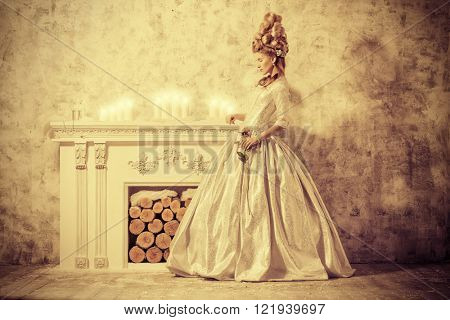 Elegant young woman in a lush medieval dress with hair in the style of the Renaissance. Sepia.