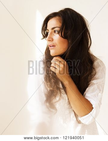 portrait of pretty young woman in white room, tenderness spring warm light