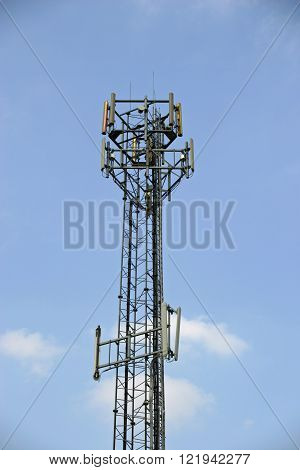 Telecommunications mast with various aerials for mobile phones. Background of blue sky with a few white clouds.