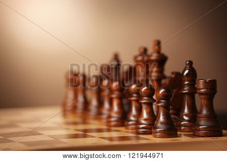 Chess pieces and game board on brown background