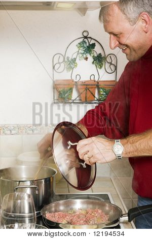 Senior or best ager man cooking dinner in his home kitchen, preparing minced meat in a pan