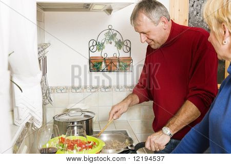 Senior or best ager couple cooking dinner together in their home kitchen, doing salad and preparing minced meat in a pan