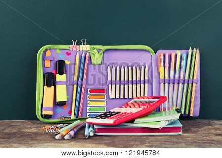 Pencil case with various stationery on old  wooden table, on blackboard background