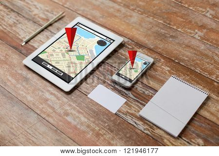 business, navigation, objects and technology concept - close up of notebook, tablet pc computer and smartphone on table