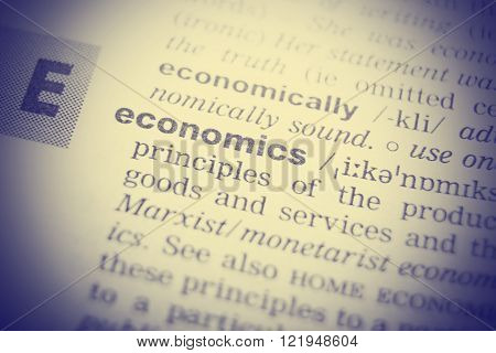 Close-up of word in English dictionary. Economics, definition and transcription
