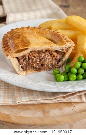 Steak or beef pie with chips or fries and green peas