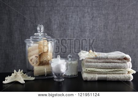 Bathroom set with towels, sponges and wisps on grey background