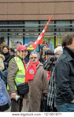 STRASBOURG FRANCE - MAR 15 2016: Woman holding red Confederation Generale du Travail (C.G.T.) as hundreds protests against Bas-Rhing Alsace departmental budget cuts for 2016 requesting no cuts and wage increase