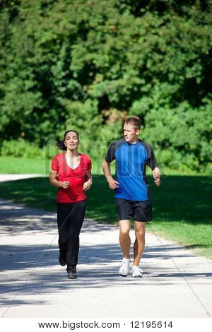 Mature woman is jogging in her free time with her young personal trainer on a sunny and warm day