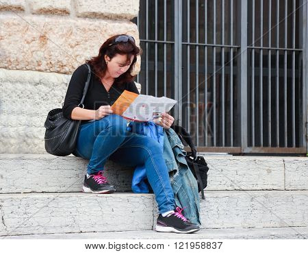 Woman sitting on the stairs and sees the tourist map