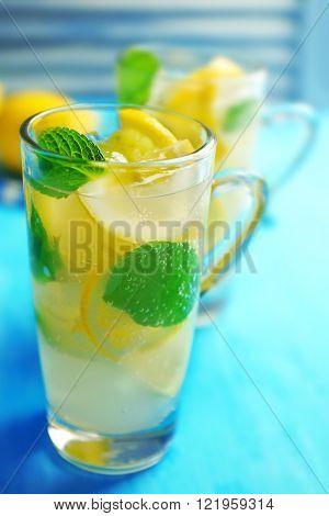 Lemonade with lemon and mint on blue table against blue jalousie, closeup