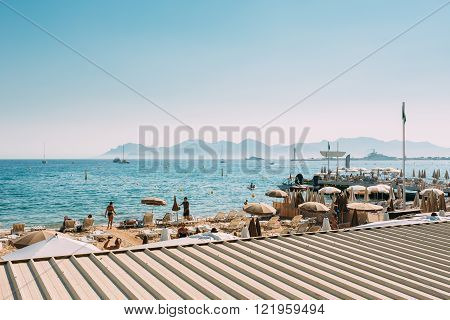 Cannes, France - June 28, 2015: Beach sun loungers. Chaise-longues on the beach. Sunbed and umbrella on beach in Cannes, France.