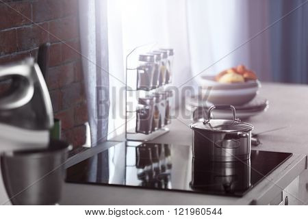 Modern electric stove with mixer, utensils and spices in the kitchen beside window