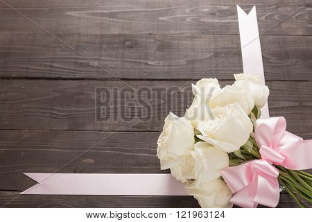 White roses flower with ribbon are on the wooden background.