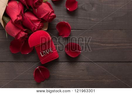 Love is beside of the red roses flower on the wooden background.