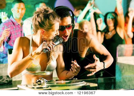 Two DJs - male and female, black and white - in a club at the turntable, in the background a crowd of their fans cheering