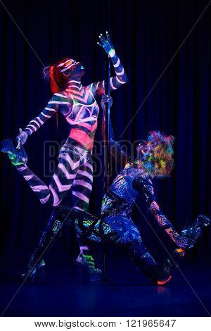 Female pole dancer in bright neon colours under ultraviolet (UV) light on background