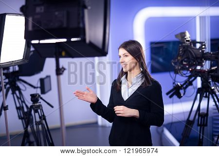 Television presenter recording in television news studio.Female journalist anchor presenting business report.News camera,light equipment behind the scenes.Talking at camera to the TV audience