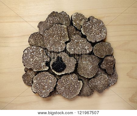 sliced black truffles (tuber aestivum) on a wooden board