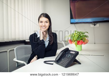 Young smiling female worker in the office.Modern entrepreneur business woman sitting in the office.Customer service representative.Bright office room.Secretary,agent,assistant,phone answering concept