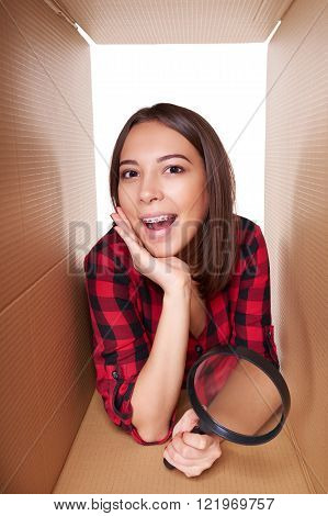 Girl opening a carton box and looking inside
