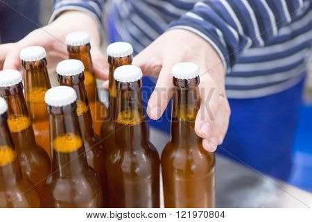 Close-up of man taking full beer bottles on a craft beer elaboration process. Unrecognizable