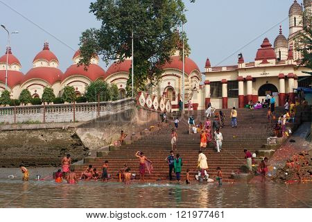 KOLKATA, INDIA - JAN 17: People wash in water of the ghat near the Dakshineswar Kali Temple at the sunny day on January 17, 2013. Holy Ramakrishna came to the temple in 1855 when it was built