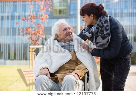 Photo of elderly man and his caring daughter