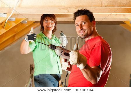 DIY couple in home improvement with hand drill standing on a scaffold