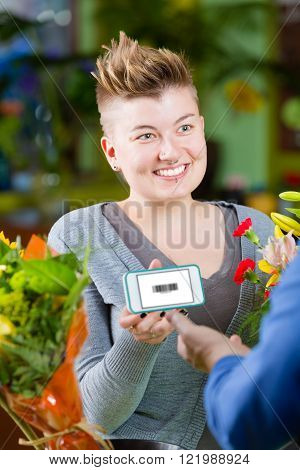 Cute female customer in store showing clerk phone with electronic coupon displayed ** Note: Shallow depth of field