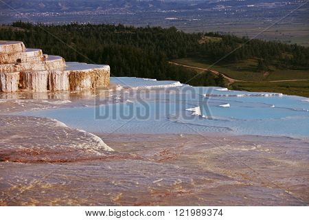 Pamukkale mineral pools overlooking valley and pine forest in Turkey