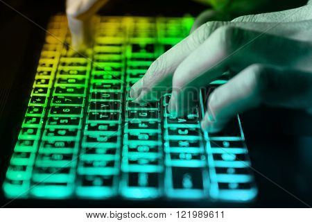 hands typing on keyboard in green light with motion blurConcept for cybercrime hack cloud security