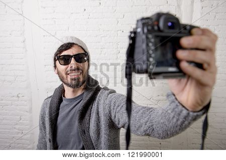 young attractive man wearing casual clothes sunglasses in hipster style modern look holding photo camera shooting self portrait selfie picture or recording video in internet blog and blogger concept