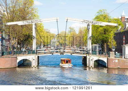 Amsterdam-April 30: Magere Brug (Skinny Bridge) as seen from the water on April 30 2015. Bridge provides a nice spot to take in sweeping views of the Amstel river with the Carre Theatre close by.