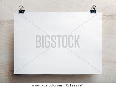 Photo of blank white paper poster hanging on light wooden background. Mock-up for design presentations and portfolios. Front view.