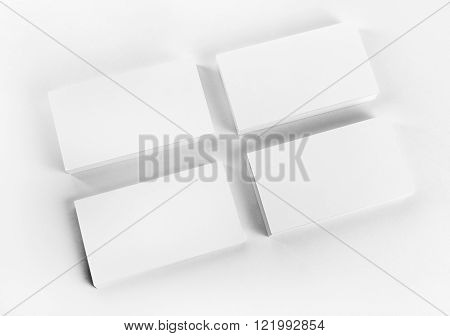 Photo of blank business cards with soft shadows on paper background. Mock-up for branding identity. Studio shot.