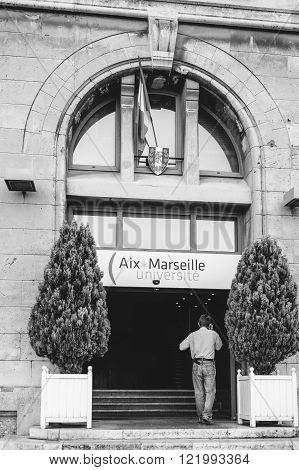 MARSEILLE FRANCE - JUL 18 2014: Blackand white image of man entering while speaking on mobile phone at the Aix Marseille University in the city of Marseille France. Aix-Marseille University is a public research university located in Provence southern Fran
