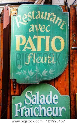 MARSEILLE, FRANCE - JUL 18, 2014: Vintage restaurant name painted on green wooden plaque showing Restaurant avec Patio Fleuri translated as Restaurant with Patio in bloom