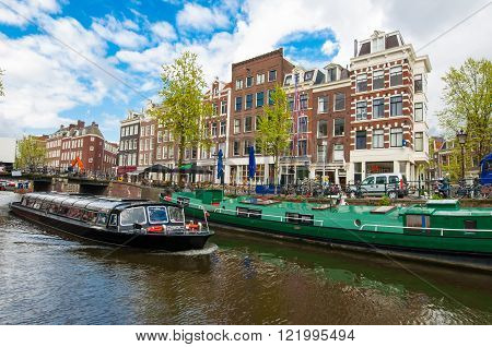 Amsterdam-April 30: Boat trip through Amsterdam canals with houseboats along the canal people enjoy sightseeing on April 30 2015 Netherlands.