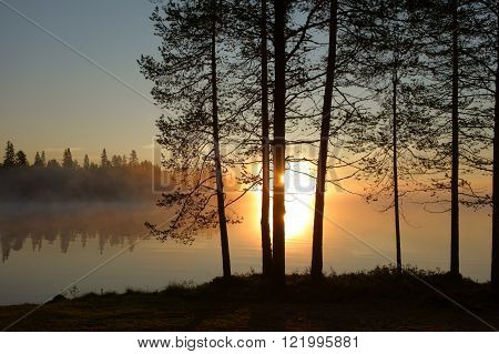 misty sunrise on a finnish lake, lapland