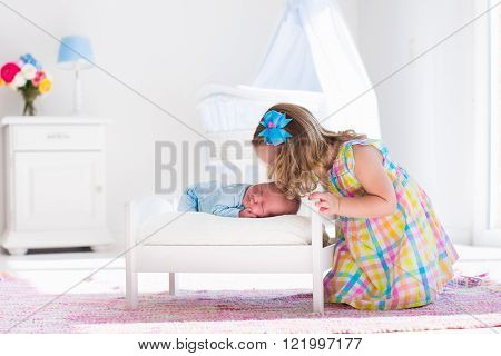 Cute little girl kissing newborn brother. Toddler kid meeting new born sibling. Infant sleeping in toy bed in white nursery. Kids playing. Siblings with small age difference. Children play and bond. poster
