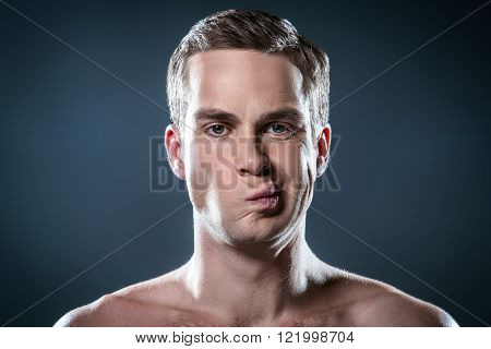 Studio portrait of handsome young man. Clean shaven and displeased man with naked torso looking at camera
