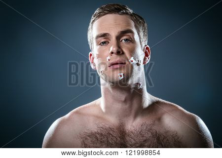 Studio portrait of handsome young man. Clean shaven man with naked torso looking at camera. His face with cuts after shaving