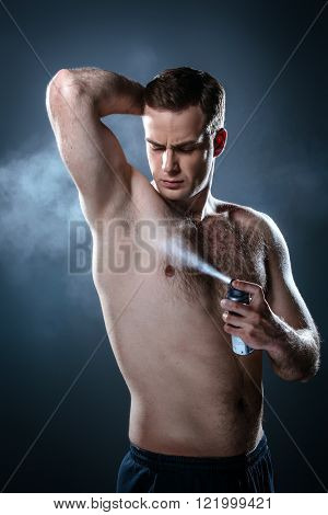 Studio portrait of handsome young man. Clean shaven man with naked torso using deodorant