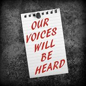 The message Our Voices Will Be Heard in red text on a scrap of lined paper pinned to a grunge background in black and white for effect poster
