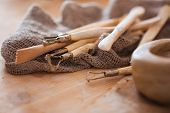 Set of dirty art and craft sculpting tools on wooden table in pottery workshop poster