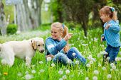 Beautiful woman with little girl and dog playing outdoors poster