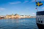 View of the harbour of Skeppsbron, the eastern waterfront of Gamla stan (the old town of Stockholm), with waving Swedish flag on moored ship in foreground poster
