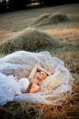 Beautiful bride relaxing in hay stack at her wedding day poster